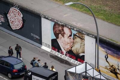 Das Bild zeigt die bemalte Mauer an der East Side Gallery. Zu sehen ist das berühmte Mauergemälde Bruderkuss. Auf diesem Gemälde  küssen sich zwei ehemalige Staatschefs der Sowjetunion und der DDR. Auf dem Gehweg vor dem Bild stehen einige Touristen und machen Fotos.