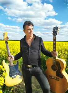 Sänger Danilo Rogoli, in einem Rapsfeld stehend, in jeder Hand eine Gitarre
