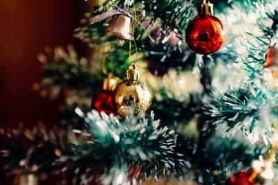 Weihnachtskugeln und Glocke hängen am Baum.